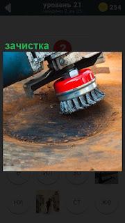 Происходит зачистка машинкой поверхности ржавой машины