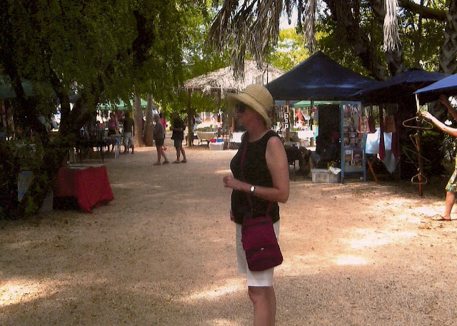 woman in shorts and sunhat in open market