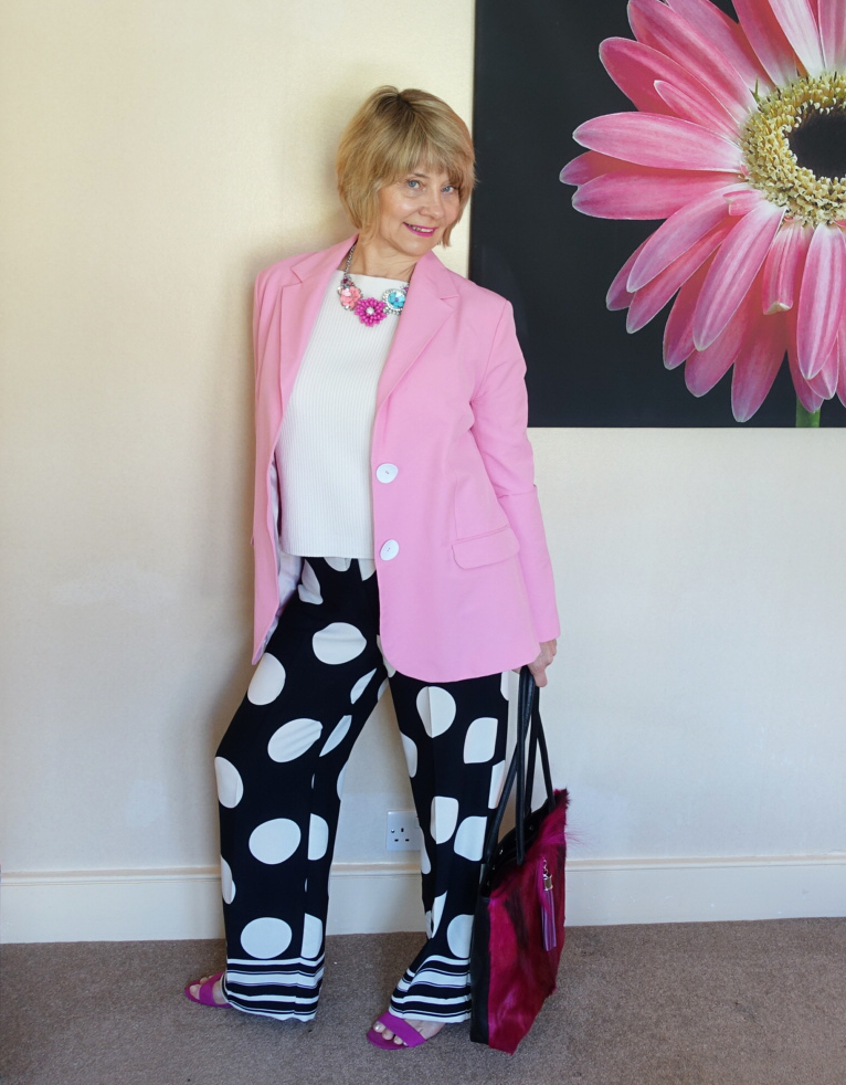 Gail Hanlon from Is This Mutton in wide legged polka dot trousers, white jumper, pink jacket and pink sandals and statement tote bag