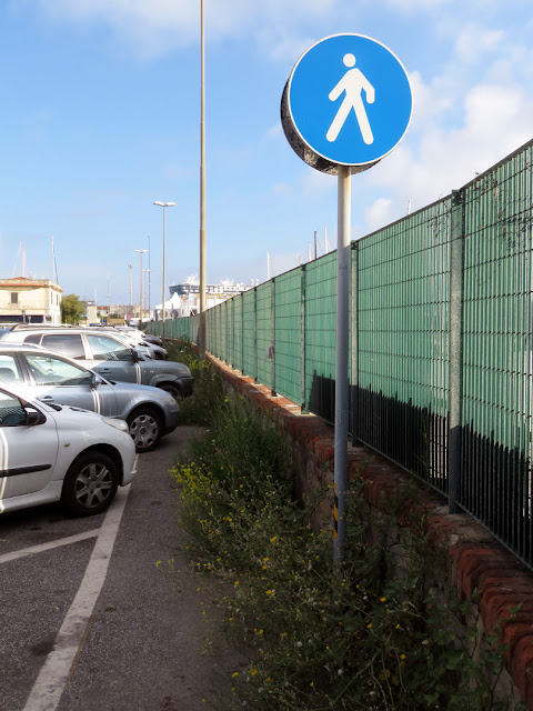 Pedestrian path invaded by cars and weeds, port of Livorno