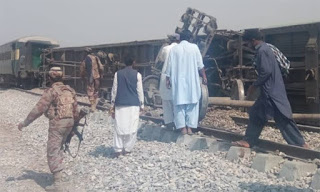 Pakistani officials examine the passenger train following twin blasts on a railway track in southwest Pakistan.
