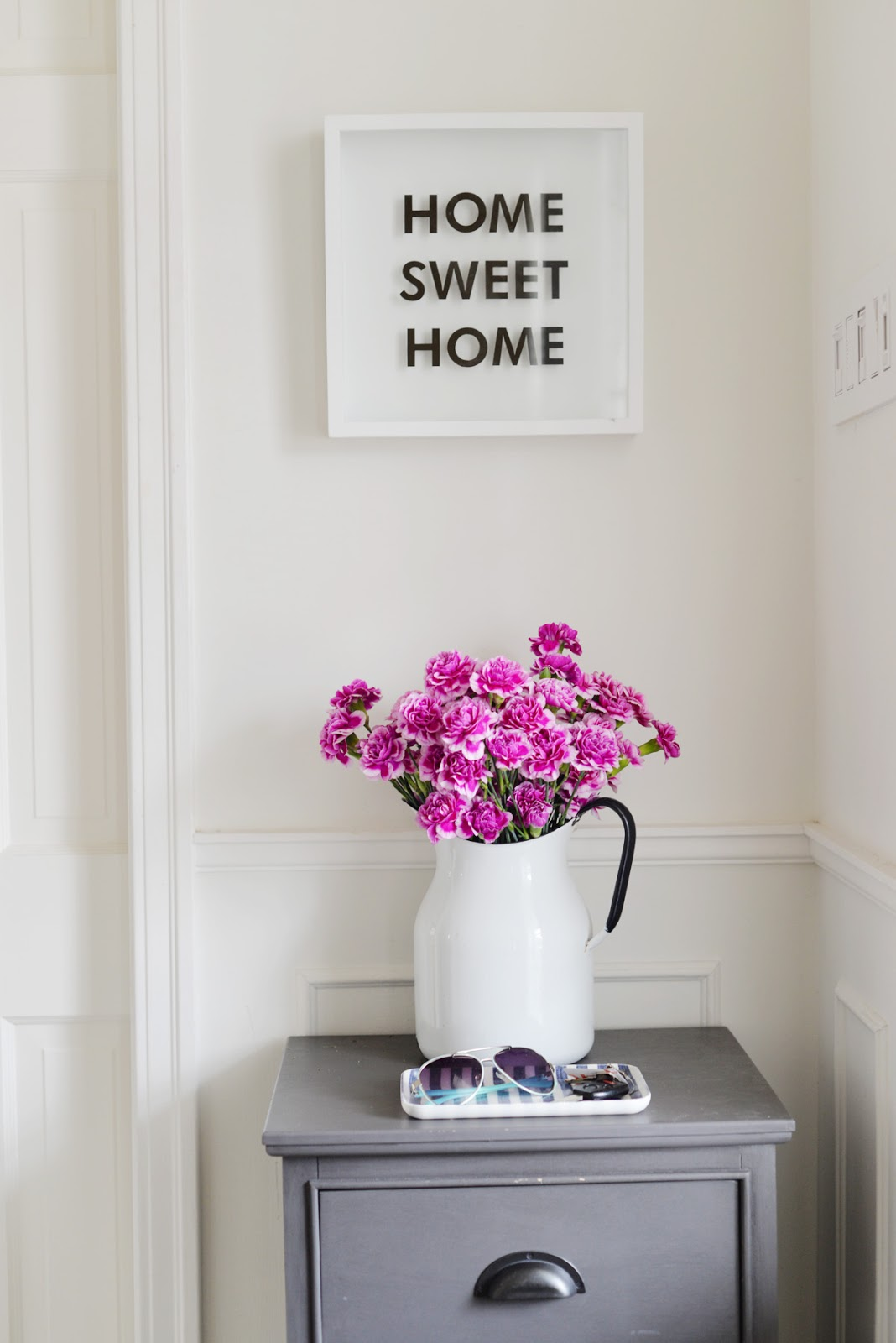 home sweet home sign, pink flowers in pitcher vase, welcoming home entry