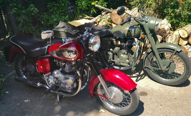A green Royal Enfield and a red Royal Enfield.