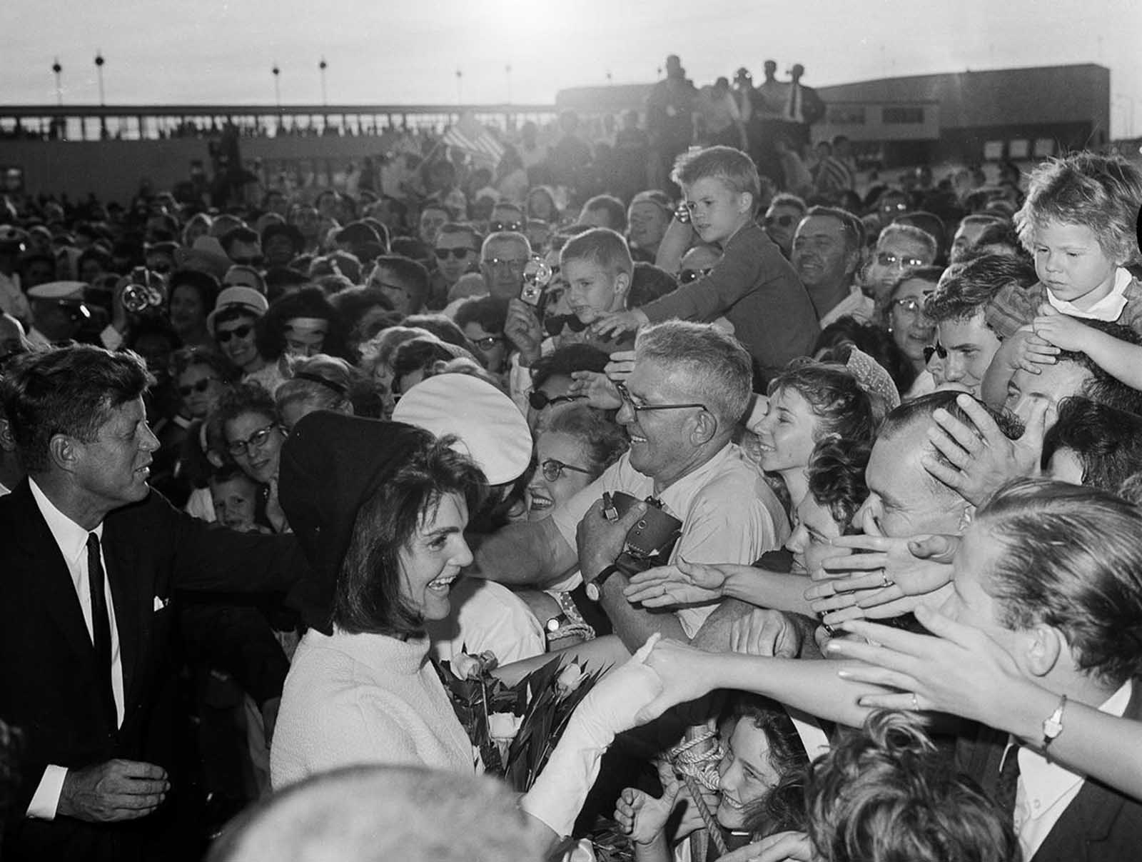On November 21, 1963, President John F. Kennedy and first lady Jacqueline Kennedy shake hands with well-wishers who lined the ramp at Houston International Airport to welcome them to the Texas city.