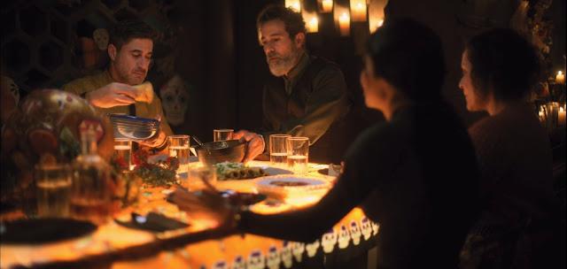 mesa decorada al estilo mexicano de la noche de los muertos, muchos vasos, platos, y bolsa con diferentes platos, imagen con todos anaranjados por la luz de las velas