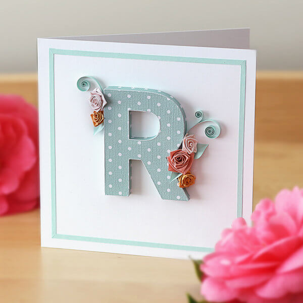Dimensional paper uppercase letter R with quilled roses and scrolls on white card