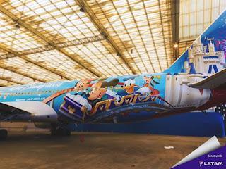 Foto diurna no interior de um hangar. Avião de perfil esquerdo, toda fuselagem foi adesivada com fundo em tons de azul que remetem ao céu. A parte traseira, a do B-767/300 da TAM ganhou uma divertida cena: Personagens da Disney estão sorridentes no trenzinho de uma montanha-russa. O trenzinho roxo com detalhes em dourado desliza sobre trilhos azuis e alcança o topo de uma curva, o contorno da cara e orelhas redondas do Mickey também em dourado estampam a parte da frente e laterais do trem. No vagão da frente,Mickey e Minnie seguidos pelo Pato Donald e por fim, Pateta sozinho no último vagão. Na cauda, o castelo da Disney em branco com as torres azuis envoltas por fogos de artifício. Na parte central da aeronave, acima das janelinha em letras brancas lê-se: Walt Disney World.