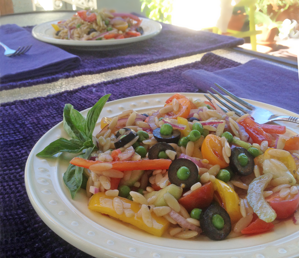Two servings of Orzo salad on salad plates and served outside.