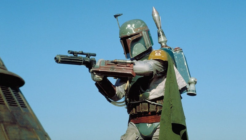 Boba Fett in armor with various accoutrements pointing a gun at something out of frame
