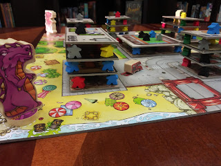 The board at the beginning of the game. A purple lizard monster stands on the corner of the board with a red monster visible on the far corner. The board is made to look like a bird's-eye view of a city; some of the spaces on this board are areas for buildings. These spaces have a meeple in each corner, with a cardboard rectangle on top of them. Four more meeples are on the corner of this rectangle, with another rectangle on top of them. This is topped by a third layer of four meeples and a rectangle; a single meeple stands in the centre of this top rectangle.