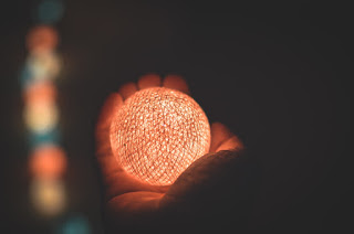 Against a dark background, a hand reaches out away from the viewer, holding a glowing ball. The hand is barely illuminated, aside from the light from the ball.