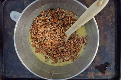 Folding in chopped pecans for pecan pie bars recipe