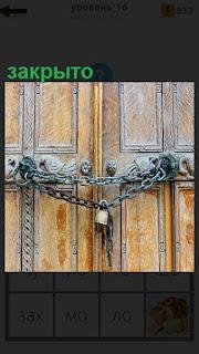 Деревянные двери на которых висит цепь и на замок закрыто