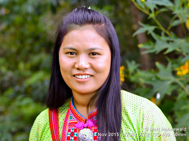 Matt Hahnewald; Facing the World; Asia; Northern Thailand; travel destination; tourism; hilltribe; ethnic minority; ethnic; young woman; world cultures; eye contact; street portrait; closeup; Nikon DSLR D3100; 50 mm prime lens; Lahu hilltribe; traditional Lahu costume; Musoe tribe; Lahu Sheleh; smiling; Lahu village; Lahu woman; Doi Hua Mae Kham; headshot; colour; Golden Triangle