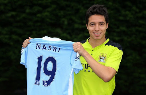 New signing Samir Nasri holds up his new Manchester City shirt during a photocall