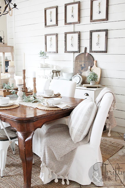 dining room with wood table, white metal chairs, white slipcover chairs, shiplap wall and wood gallery wall.