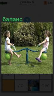 Две девочки на качелях сохраняют баланс играя между собой