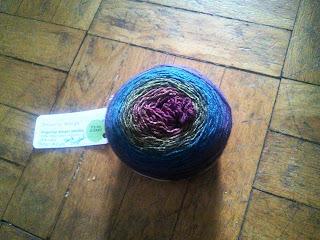A cake of yarn ranging from dark blue to dark red.