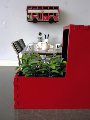 Modern one-twelfth scale miniature cafe with a concrete floor and a bright red planter box filled with plants. On the wall above the table is a vintage model Routemaster bus.