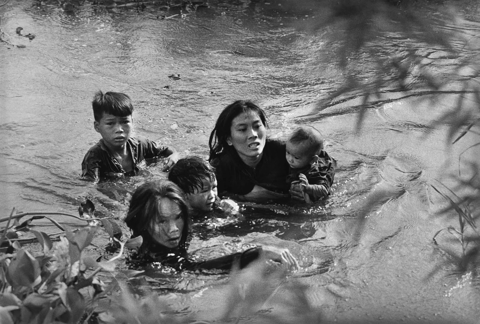 A Vietnamese mother and her children wade across a river, fleeing a bombing raid on Qui Nhon by United States aircraft on September 7, 1965.