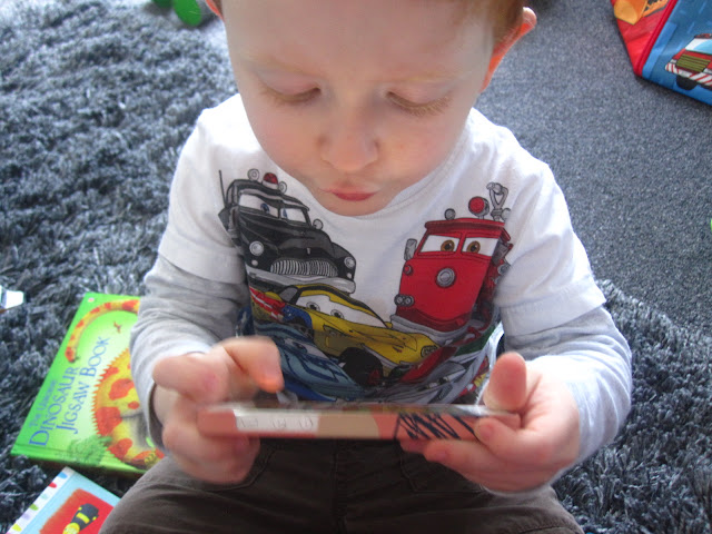 Little boy surrounded by books and holding a phone