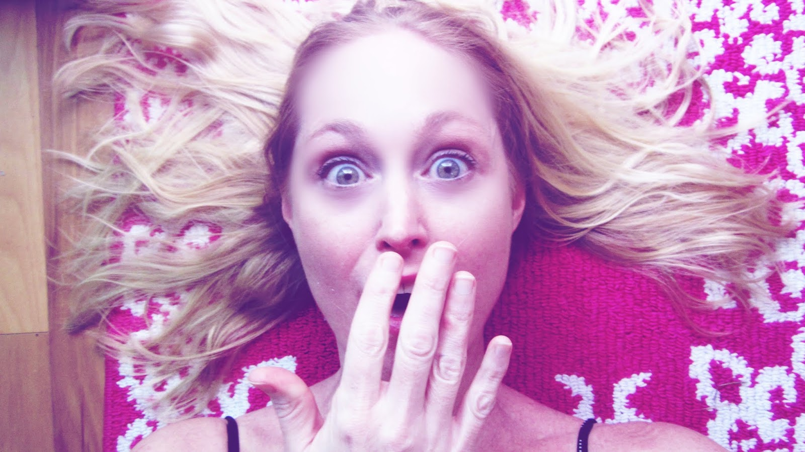 Woman With Blonde Hair on Pink Rug With a Surprised Look