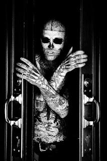 Hombre completamente tatuado estilo zombie saliendo de un sarcófago.