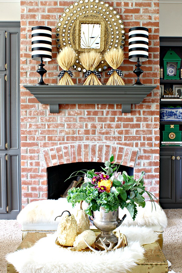 brick fireplace, peacock mirror, brass trunk, striped lampshades