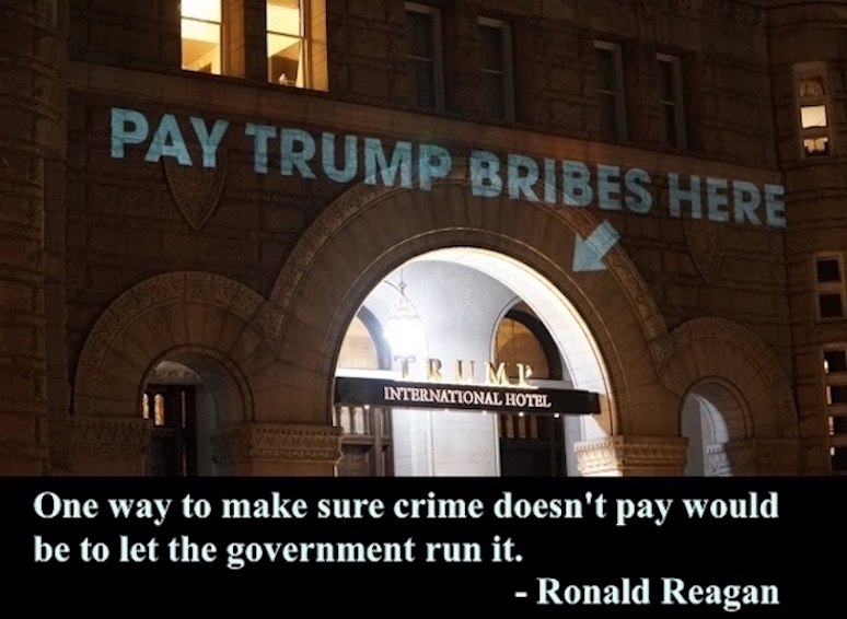 "Trump International Hotel, in Washington, D.C., first day of business Sept. 12, 2016. ""Pay Trump bribes here"" projected by the artist Robin Bell on May 16, 2017"