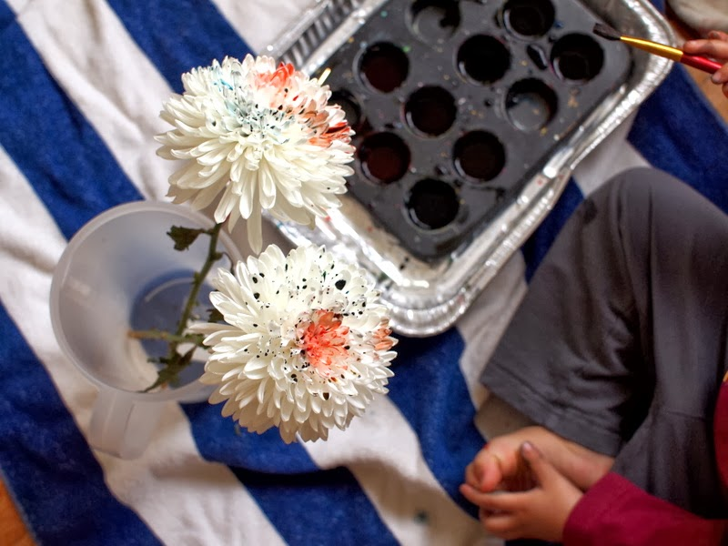Use food coloring to paint white flowers rainbow colored
