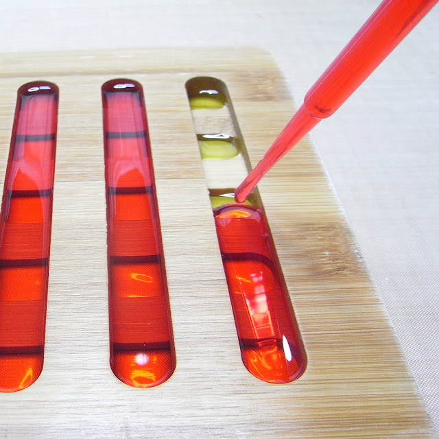 Using a pipette to transfer coloured resin into the slots of a bamboo trivet.