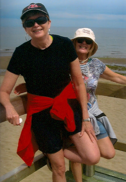 two woman laughing with beach behind them
