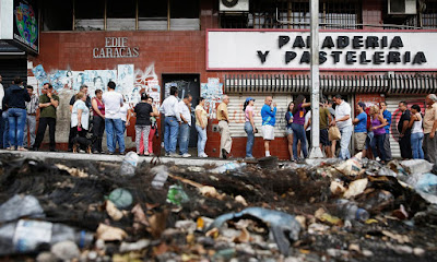 picture of crows waiting in line for any leftover food at a Venezuelan supermarket. In the foreground, garbage abounds.