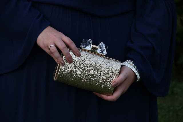plus size navy maxi dress and ted baker gold glitter clutch bag image