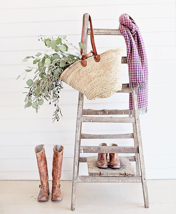 Ladder with French market basket and riding boots in romantic Farmhouse Christmas vignette