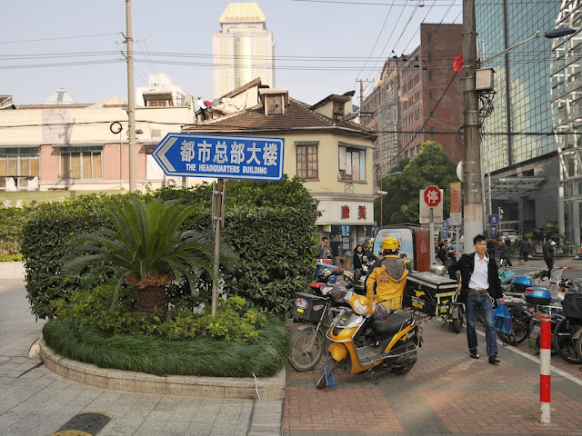 Scene along Guangdong Road including a directional sign to The Headquarters Building in Shanghai