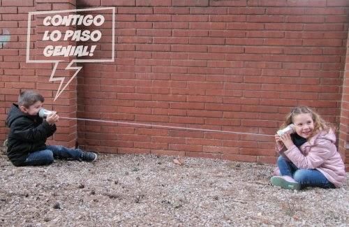 Niños utilizando el teléfono con latas