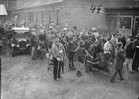 A black and white photograph of a crowd of figures outside. Most are visibly holding shovels, hoes, and other tools.