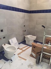 Two incomplete toilets being installed in the men's room.