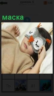 На кровати спит ребенок с маской на лице в форме совы с кисточками сверху и клювом внизу