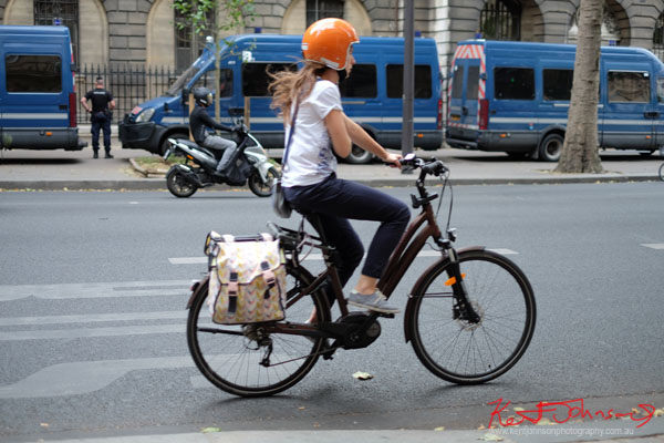 Woman rides a ladies bike with panners wearing an orange motorbike style helmet. Paris photos by Kent Johnson for Street Fashion Sydney.