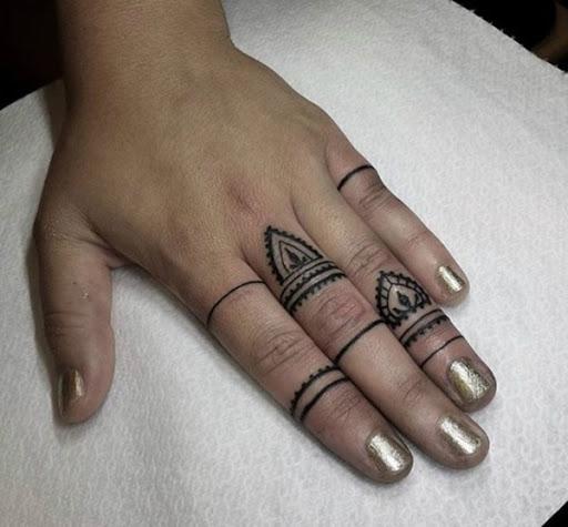 Faixas em preto e elementos de mandalas são usadas para criar o anel como desenhos enrolado em torno do utente dedos neste tatuagem.