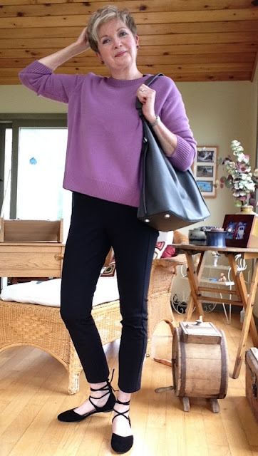 woman in black pants, pink sweater, black flats and grey tote bag.