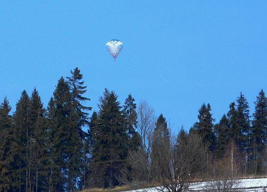 Nad lasem widać balon niesiony prądami powietrza.