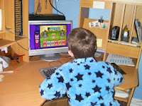 kid in starry dressing gown playing friv online games