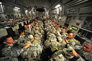 blog picture of soldiers on a plane with their back packs on their laps