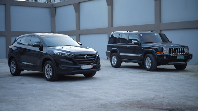 Black Hyundai Tucson with black grills beside a Jeep Commander front right quarter view