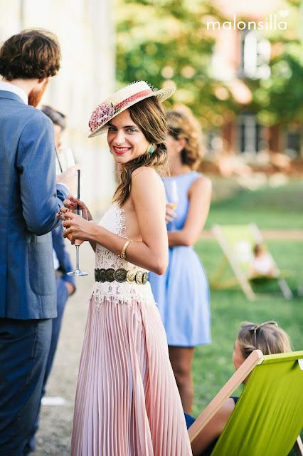 Invitada boda con falda plisada larga rosa palo, top encaje color blanco, sombrero canotier de ala ancha en burdeos y tapafeas marca malonsilla con peinado de coleta ladeada