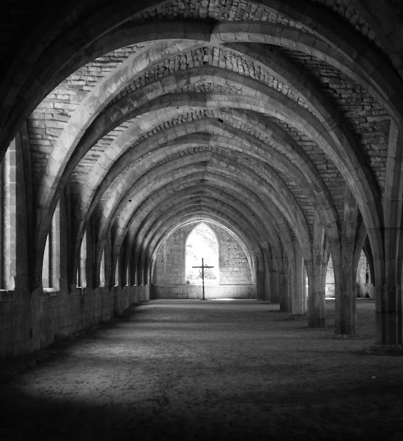 a black and white photo of an arched stone corridor in fountains abbey, with a crucifix silhouetted in the window at the end