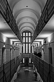 Black and white photograph of a Victorian prison interior with whitewashed walls and vaulted ceiling and two tiers of metal railings forming balconies. The middle balcony is at the level of the photograph point of view and shows cell door openings on both sides. There are figures in the middle distance of the image on the central balcony, looking into a cell.